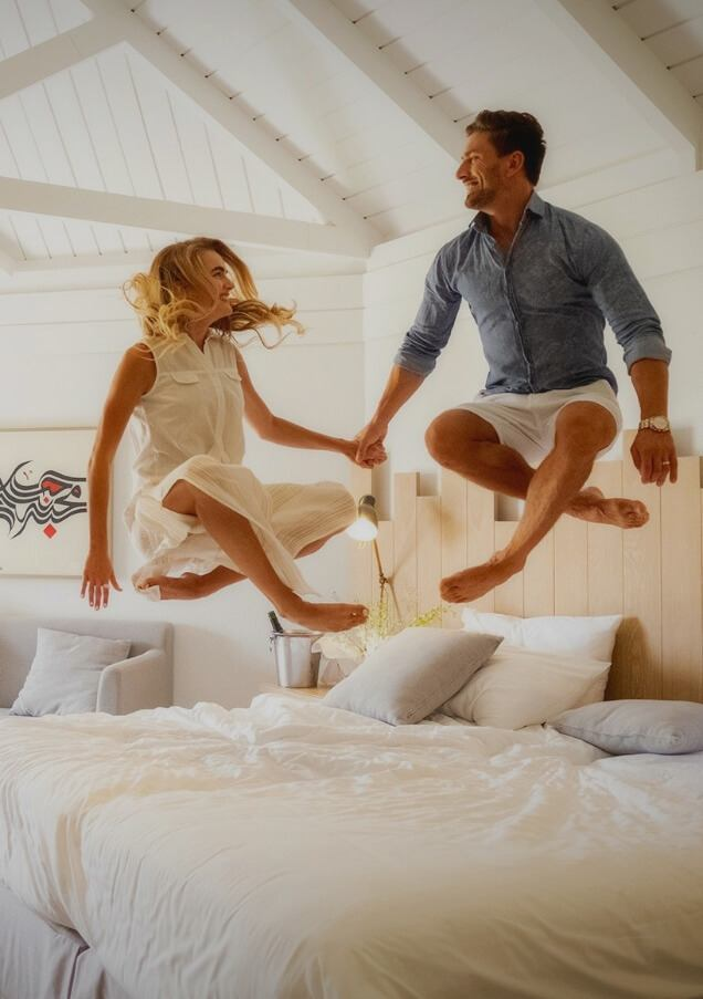 Couple Jumping on King Bed