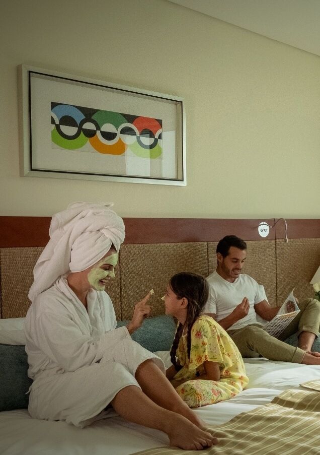 Family Lounging In Hotel Room Bed
