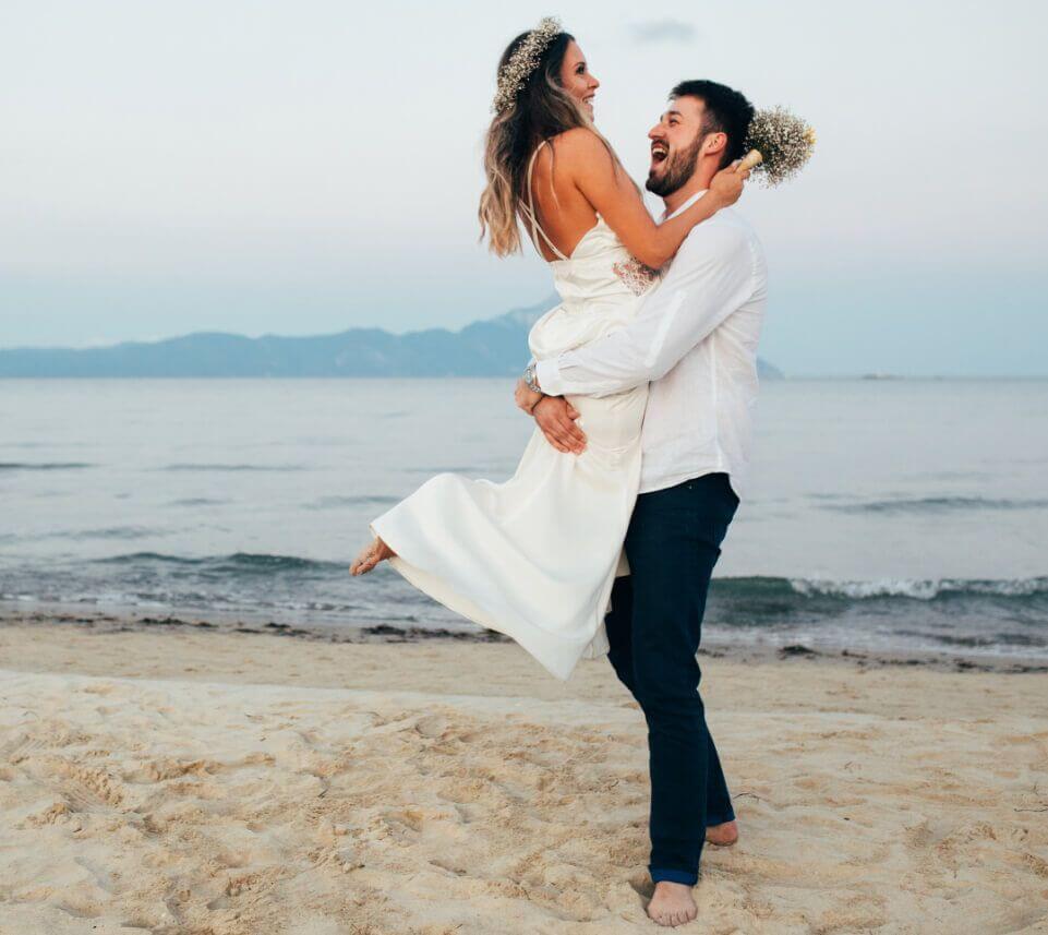 Groom Lifting Bride on Beach