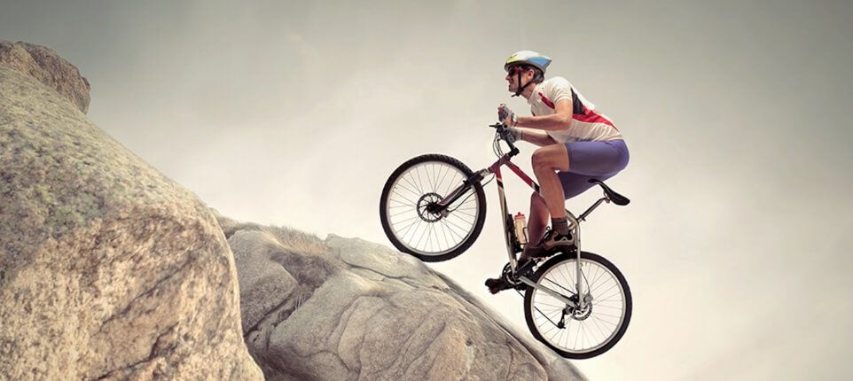 Man Biking up Boulders