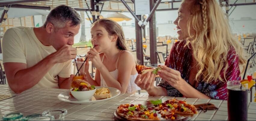 عائلة تتناول البرجر والبيتزا